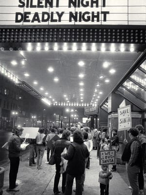 """Nicole Olivo, 2, stands with her father, David, as they and other demonstrators protest the showing at the Grand Theater of """"Silent Night, Deadly Night,"""" on Nov. 9, 1984, a movie about a homicidal maniac dressed as Santa Claus. This photo was published in the Nov. 10, 1984, Milwaukee Sentinel."""