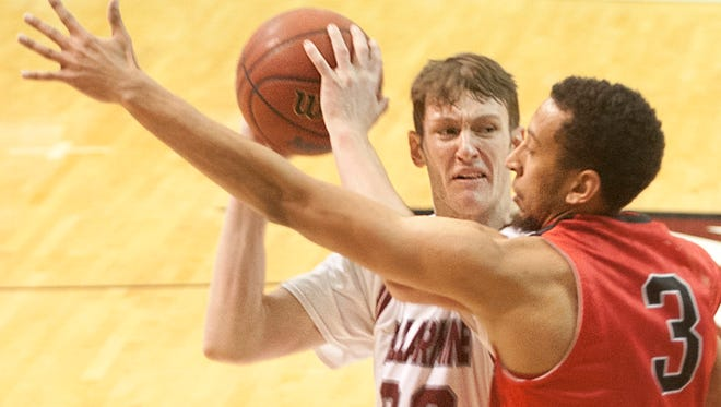 Bellarmine Knights forward Josh Derksen looks for a path to the basket as he is guarded by William Jewell Cardinals guard Christian Hildebrandt. Bellarmine defeated William Jewell, 70-50.04 January 2015