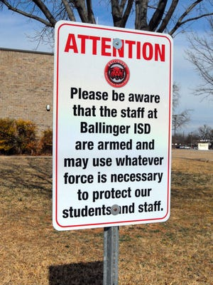 A sign warns visitors that staff at Ballinger Independent School District are armed and will used force to defend students and staff.
