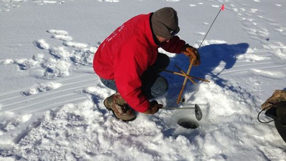 Ed Mackin uses a ladle to clear ice from a fishing hole.