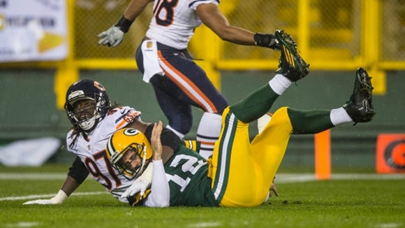 Nov 26, 2015; Green Bay, WI, USA; Chicago Bears linebacker Willie Young (97) tackles Green Bay Packers quarterback Aaron Rodgers (12) during the NFL game on Thanksgiving at Lambeau Field. Chicago won 17-13.
