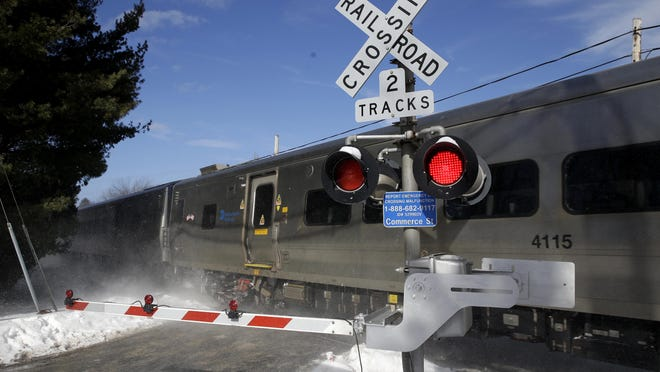 A train passes through the intersection where an SUV was struck by a Metro-North Railroad train in Valhalla on Feb. 5. The fiery crash killed a motorist and five rail riders.