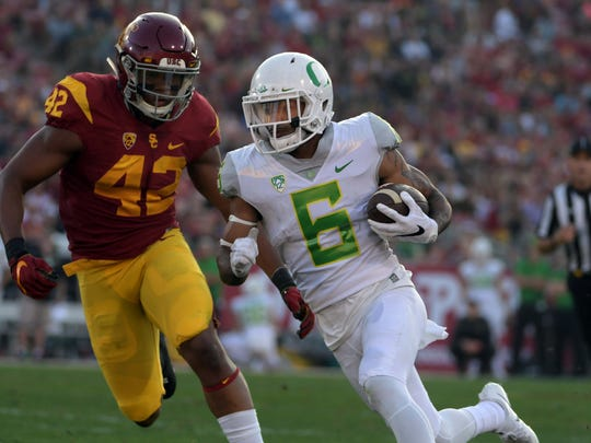 Nov 5, 2016; Los Angeles, CA, USA; Oregon Ducks wide receiver Charles Nelson (6) is defended by Southern California Trojans linebacker Uchenna Nwosu (42) on a 25-yard touchdown run in the first quarter during a NCAA football game at Los Angeles Memorial Coliseum. Mandatory Credit: Kirby Lee-USA TODAY Sports