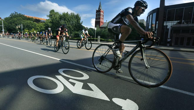 Cyclists ride down Court Street during the Rochester Twilight Criterium.