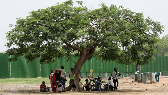 People sit under the shade of a tree during a hot afternoon in New Delhi, India, on April 27, 2018. According to weather reports, some parts of Delhi soared to 108 degrees.