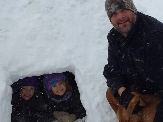 "From grandmother Margene Berdine via email: ""Haley, Zoey, Daddy and Wilma showing off the igloo they built in Russellville, Indiana."""