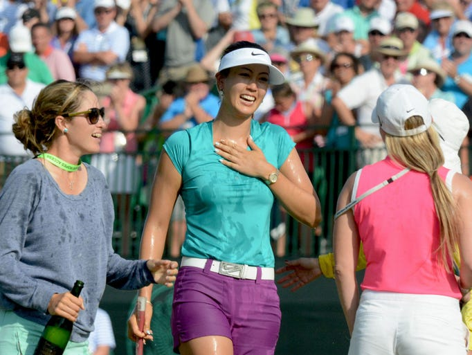 Michelle Wie (center) is congratulated by golfer Jaye Marie Green (left) and manager Jamie Kuhn (right) after winning the U.S. Women's Open at the Pinehurst Resort and Country Club.