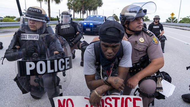 BOCA RATON -- Florida Highway Patrol Capt. Roger Reyes takes a knee with demonstator Vell Remy in the middle of Glades Road that was shut down to prevent the marchers from going on to Interstate 95 while protesting the death of George Floyd on Monday.