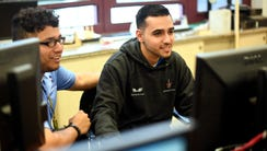 Mohamad Chacha, right, a Syrian refugee, works on Rutgers