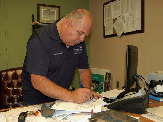 Bull Shoals Mayor David Hotchkiss signs Friday night some of the paperwork from the U.S. Department of Agriculture awarding the city the combination of a grant and a loan to build a new wastewater treatment facility.