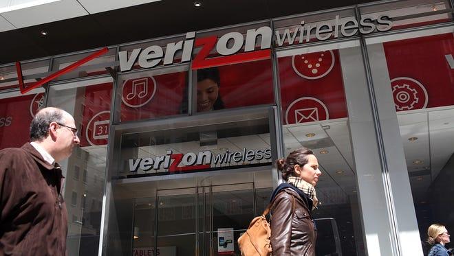 Pedestrians walk by a Verizon Wireless store on April 19, 2012 in New York City.
