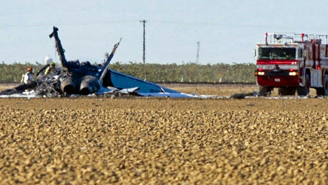 Firefighters stand by wreckage from a fighter jet where it crashed in a field near Lemoore Naval Air Station in California on Sept. 21, 2015. The pilot ejected and safely parachuted to the ground.