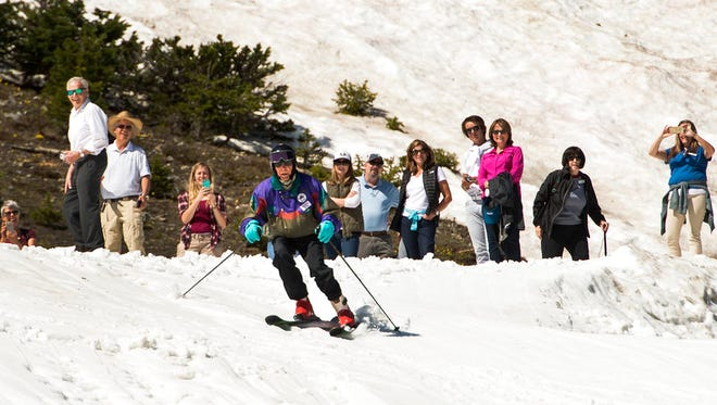 In this July 5, 2017 photo, Skier George Jedenoff celebrates his 100th birthday with a couple of ski runs down Chip's Run from the top of the Peruvian Lift at Snowbird Resort, Utah, surrounded by friends and family.
