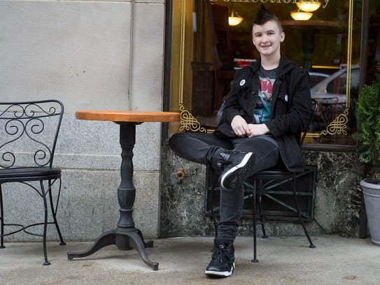 Rory Philbrick sits outside World Coffee Cafe in downtown