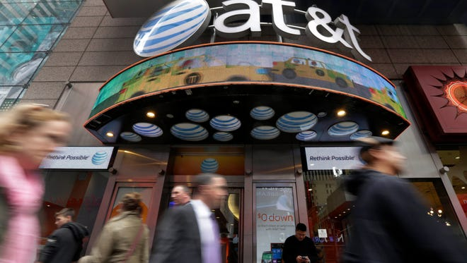 In this Oct. 21, 2014 photo, people pass an AT&T store in New York's Times Square. AT&T reports quarterly financial results on Tuesday, Jan. 27, 2015. (AP Photo/Richard Drew) ORG XMIT: NYBZ314