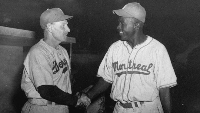 Dodgers manager Leo Durocher, left, shakes hands with Jackie Robinson of the Montreal Royals before an exhibition game in Havana on March 31, 1947.
