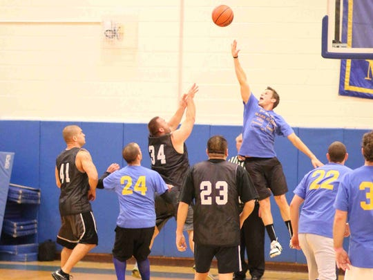 Readington teachers trounce police in Memorial basketball  game. Teacher Ryan Newcamp attempts to block the shot made by Sgt. Christopher Heycock #34.