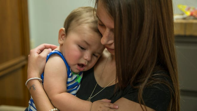 Mara Mancini, 21, holds her son, Kyson Clark, in the law offices of Saeed and Little LLP on Aug. 3, 2016. Mancini was seven months pregnant when she was attacked by an Indianapolis Metropolitan Police Department K-9 that was chasing a suspect in July 2015.