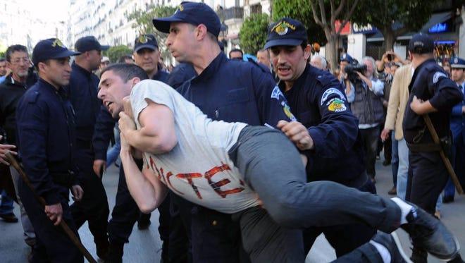 Algerian police arrest a protester belonging to the Barakat Movement during a demonstration against President Bouteflika Abdelaziz  on April 16.