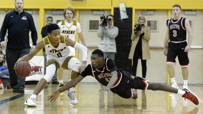 Greece Athena's Christian Jones, left, shields the ball before Hilton's Tah'Jae Hill can dive in for the steal during a regular season game at Greece Athena High School on Monday, Jan. 22, 2018. Greece Athena beat Hilton 70-48.