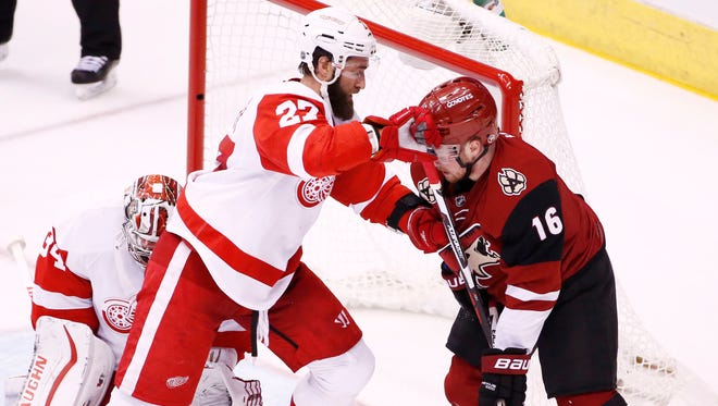 Arizona Coyotes' Max Domi takes a stick to the face from Detroit Red Wings' Kyle Quincey in the second period on Jan. 14, 2016, in Glendale.