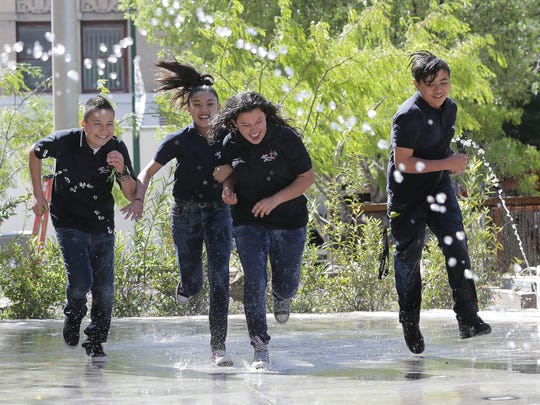 Students from La Fe Preparatory School play in the splash pad Saturday at San Jacinto Plaza during the park's grand reopening.