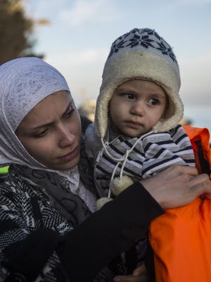 A woman takes a life vest off a baby, shortly after crossing the Aegean Sea on a dinghy with other refugees and migrants from Turkey to the Greek island of Lesbos in December.