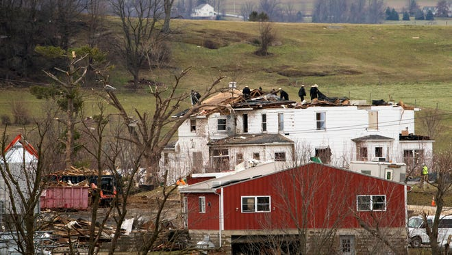 People clean up in the aftermath of a storm Thursday in Gap, Lancaster County. A tornado touched down near this area, in Salisbury Township, Wednesday night, the National Weather Service said.
