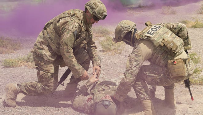 Explosive Ordnance Disposal Airmen check for life-signs on a simulated casualty during a Tactical Combat Casualty Care exercise at Holloman Air Force Base, N.M., on April 31, 2017. The training focuses on individual trauma, tools, techniques, and treatment procedures. The exercise also included the use of moulage, non-lethal training munitions, trained role-players, and a multitude of other artificial stressors.