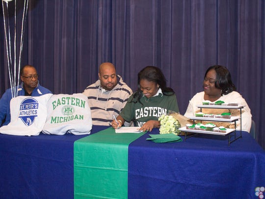 St. Peter's track star Alysse Wade signs her national letter of intent to attend Eastern Michigan University as her parents, Robert Wade and Eileen Petty, look on along with St. Peter's coach Bruce Woodson.