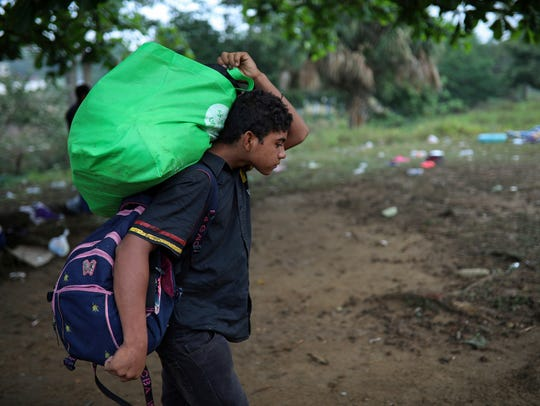 A young man carries his baggage as Central American