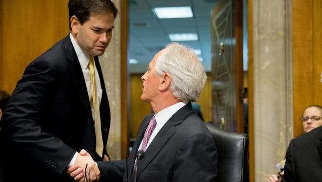 Senate Foreign Relations Committee Chairman Sen. Bob Corker, R-Tenn., center, shakes hands Republican presidential candidate Sen. Marco Rubio, R-Fla., left, after the Senate Foreign Relations Committee passes S.615, the Iran Nuclear Agreement Review Act of 2015, during a committee business meeting on Capitol Hill in Washington, Tuesday, April 14, 2015. Republican and Democrats on the Senate Foreign Relations Committee reached a compromise Tuesday on a bill that would give Congress a say on an emerging deal to curb Iran's nuclear program. (AP Photo/Andrew Harnik)
