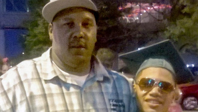 Terrill Thomas (left) is shown with his 20-year-old son, also named Terrill, at his son's high school graduation in 2014.