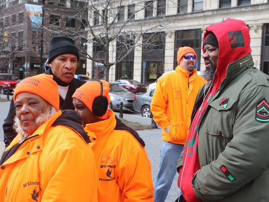 Wilmington Black Lives Matter founder Mahkieb Shabazz Booker (right) talks to members of the Wilmington Peacekeepers (in orange) and the Rev. Derrick Johnson of Joshua Harvest Church before a rally Saturday at Rodney Square in downtown Wilmington.