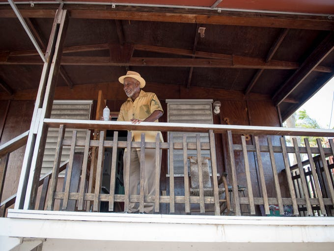 Modesto Cepeda stands on the patio of his house, which