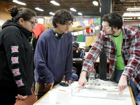 Students from Detroit Hispanic Development Corporation's 5756 REC'in Crew Nadia Enriquez and Emmanuel Salcido brainstorming manipulator design with Tyryn Crow, a mechanical engineer from Denso Corporation, in February 2018.