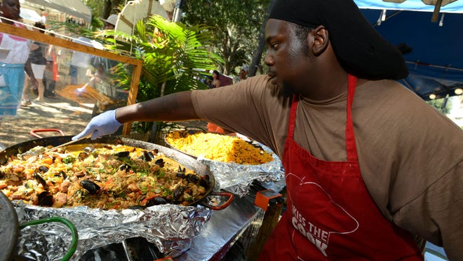 Kelvin Gaston stirs a pan of seafood paella at the Taste and Tell food stand during a past Pensacola Seafood Festival. The event returns Friday.