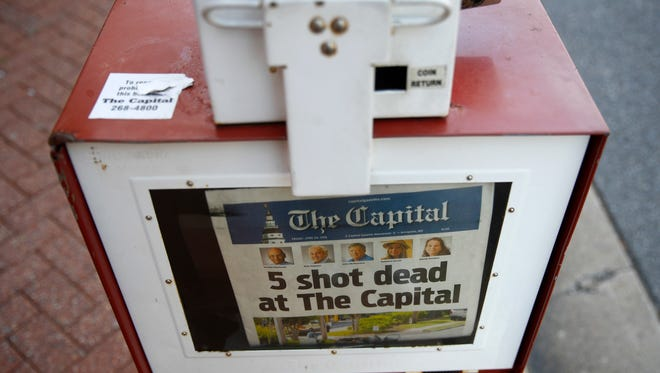 A Capital Gazette newspaper rack displays the day's front page, Friday, June 29, 2018, in Annapolis, Md.