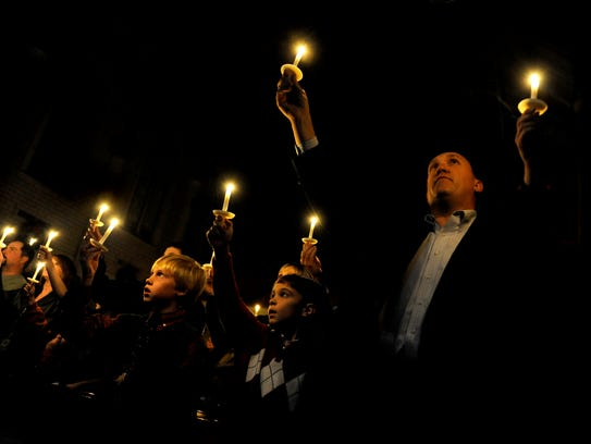 """Congregants hold candles high while singing """"Silent"""