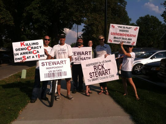 Rick Stewart and his supporters rally outside of Simpson College to raise awareness for his campaign.