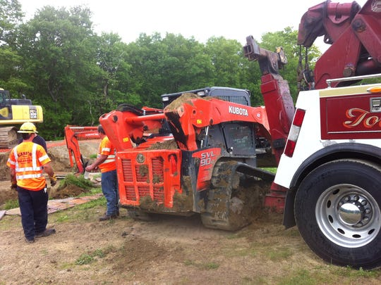 A man operating an excavator ended up upside down in a deep ditch Saturday, May 31, 2014.  He was not seriously injured but the incident drew about 50 emergency workers to the Brewster work site.