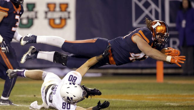 Illinois linebacker Mason Monheim, top, scores a touchdown after after intercepting a pass as Northwestern wide receiver Austin Carr tackles during the second half. Northwestern won 24-14. (AP Photo/Nam Y. Huh)