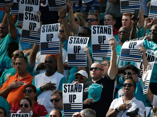 Fans show how they feel about players that don't stand for the national anthem during the first half of an NFL football game between the Miami Dolphins and the San Francisco 49ers on Sunday, Nov. 27, 2016, in Miami Gardens.