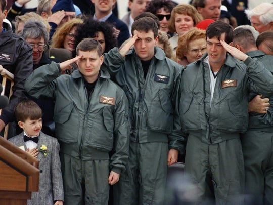 Navy Lt. Jeffrey Zaun (left), Navy Lt. Randolph Slade (center) and Navy Lt. Robert Wetzel salute during a ceremony at Andrews Air Force Base March 10, 1991 in Maryland for the former prisoners of war. Wetzel salutes left-handed due to a broken right arm.
