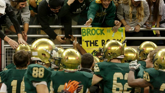 Muskegon Catholic Central celebrates with its fans after a 7-0 victory over Waterford Our Lady of the Lakes in the MHSAA Division 8 state football championship at Ford Field in Detroit on Friday, Nov. 27, 2015.