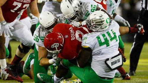 Oregon defenders swarm over USD running back Trevor Bouma in the Coyotes 62-13 loss to the Ducks in Eugene.