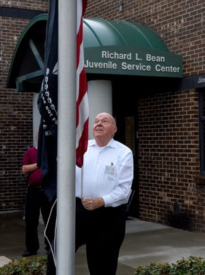 Richard L. Bean raises the flag at the Juvenile Service Center on March 7, 2017. Bean ceremoniously raises the flag every morning he works.