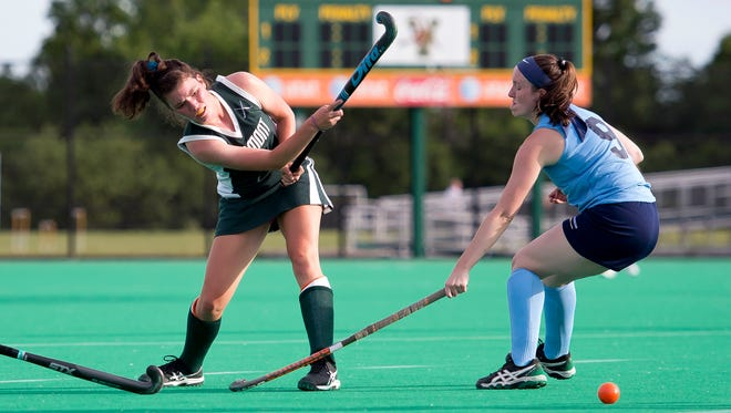 South Burlington's Joan Vera, left, sends a pass beyond the reach of New Hampshire's Maeve McPhail during the second half of the 35th annual Twin State field hockey game at Moulton Winder Field on Friday. Vermont won 4-1.