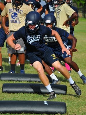 The Holy Trinity football team works out during a practice session last week. The opener is Aug. 29 vs. Father Lopez.