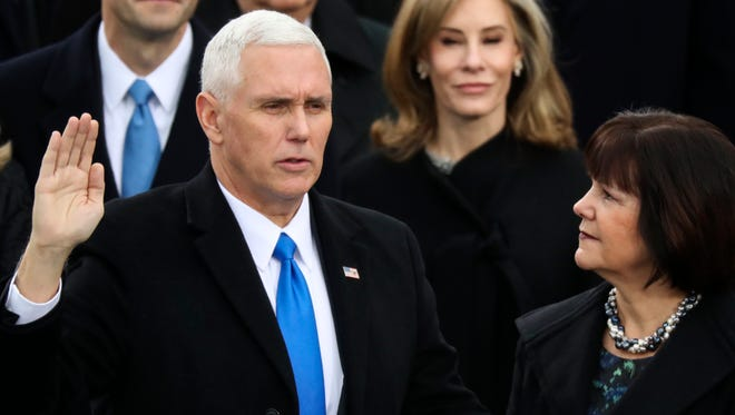 Vice President Mike Pence is sworn in as his wife, Karen, holds the Bible at the U.S. Capitol in Washington, D.C., on Friday, Jan. 20, 2017.